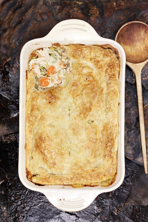 Above view of fresh Chicken Pot Pie with wooden spoon. Section of pot pie removed to reveal chicken, carrots and peas.                       photo