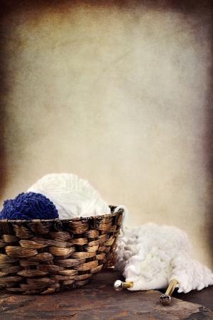 gomitoli di lana: Cesto di morbide palline di filato con cucito e ferri da calza che si trovano nelle vicinanze. Camera per copia spazio.
