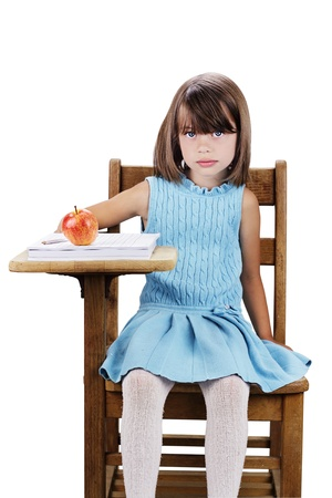 school desk: Little girl sitting at a school desk with apple and books. Isolated on a white background. Stock Photo