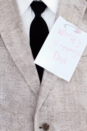 Mans suit jacket, tie and shirt with Worlds Greatest Dad note pinned over his heart.  photo