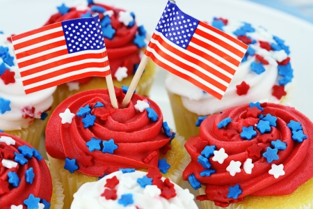 American patriotic themed cupcakes for the 4th of July. Shallow depth of field with selective focus on flags and center cupcake.