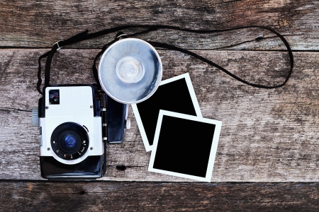 Vintage camera with blank photos on a rustic background. Clipping path in photos included.  photo