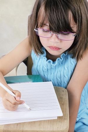 Little girl sitting at a school desk writing.