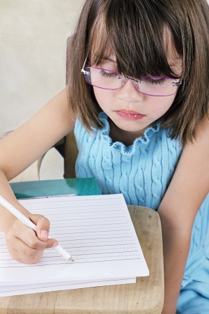 Little girl sitting at a school desk writing. photo