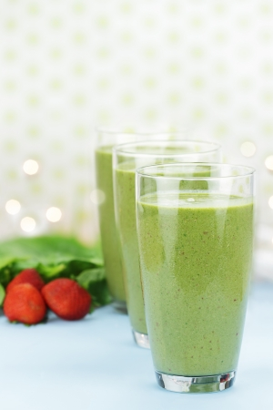 fruit smoothie: Delicious freshly made Spinach and Strawberry smoothies made with cold milk, yogurt, spinach and strawberries. Extreme shallow depth of field with selective focus on glass in foreground.  Stock Photo