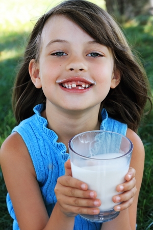age 5: Little girl drinking milk with a milk mustache. Shallow depth of field with selective focus on little girls face. Stock Photo
