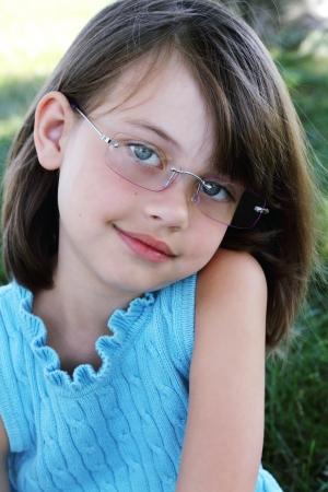 Meisje draagt een bril en direct kijken op viewer. Ondiepe diepte van gebied met selectieve focus op het gezicht van het kind. Stockfoto