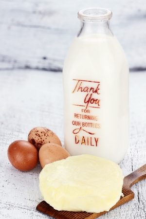 Farm fresh milk, butter, and eggs against a rustic background. Milk is in a vintage glass milk bottle. Shallow depth of field. Stock Photo - 14234027
