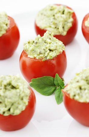 Stuffed Tomatoes filled with a pesto and avocado mixture  Extreme shallow depth of field with selective focus on center tomato  Stock Photo