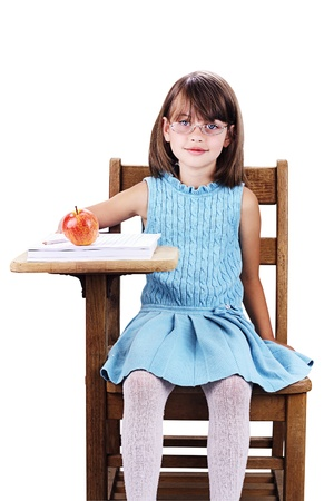 Little girl wearing glasses sitting at a school desk with apple and books  Isolated on a white background with clipping path included  photo
