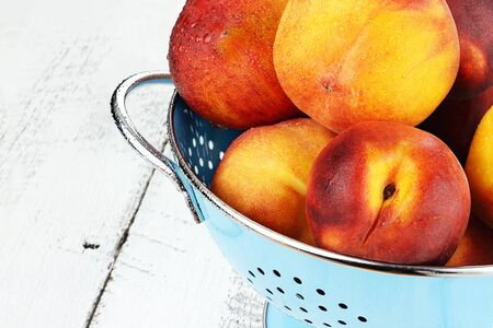 Blue colander filled with freshly washed peaches over a rustic background.