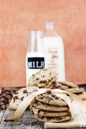 Fresh homemade chocolate chip cookies with chocoate chips and milk in antique milk bottles in the background photo