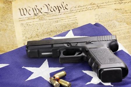 pistole: Una pistola calibro 45 e munizioni che poggia su una bandiera piegato contro la costituzione degli Stati Uniti Archivio Fotografico
