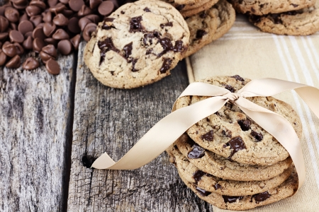chocolate chip cookies: Fresh homemade chocolate chip cookies with chocoate chips and more cookies in the background. Shallow depth of field.   Stock Photo