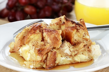 French toast casserole with maple syrup. Made with cream cheese cheese in the center. Fresh grapes and orange juice in background. Extreme shallow depth of field with selective focus on French toast.