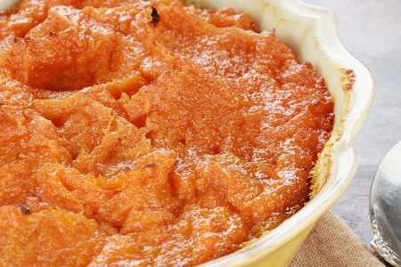 Sweet potato casserole. Extreme shallow depth of field with selective focus on center on potatoes.   Imagens