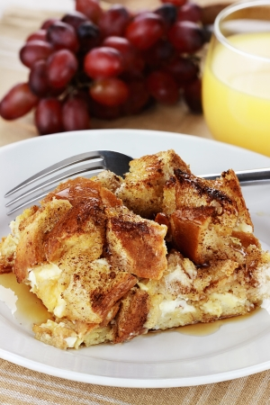 French toast casserole with maple syrup. Made with cream cheese cheese in the center. Fresh grapes and orange juice in background. Extreme shallow depth of field with selective focus on French toast.   Imagens