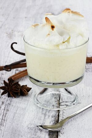 glass topped: Rice pudding in a glass bowl topped with meringue. Star anise, cinnamon bark and vanilla pods are in the background.