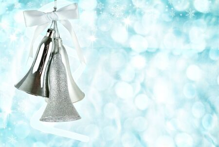 silver bells: Silver bells hanging against an abstract background of icy blue holiday lights.