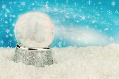 Snow globe with snow covered pine trees inside. Copy space available. photo