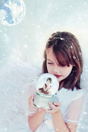 Little angel holds a snow globe and watches a little girl inside blowing snow.