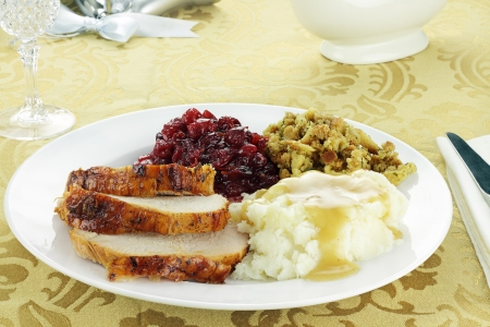Thanksgiving turkey dinner with mashed potatoes and gravy, stuffing, and homemade cranberry sauce. Stock Photo