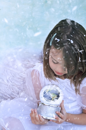 Little angel in the snow holds a snow globe and watches the earth.