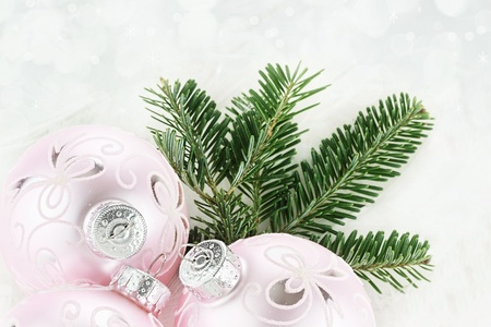 New pink Christmas baubles border with fresh pine over a white sparkly background.  Stock Photo - 16822111