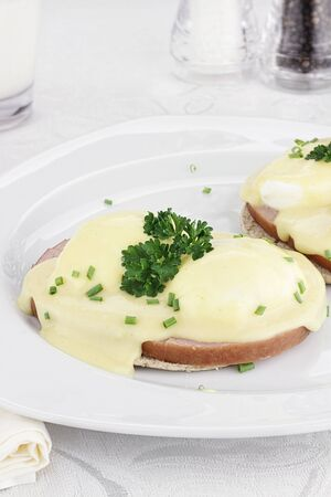 Breakfast of Egg Benedict and ham with Hollandaise sauce over sandwich thins. Stock Photo