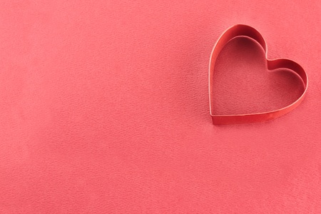 cookie cutter: Heart shaped cookie cutter over a red background. Stock Photo