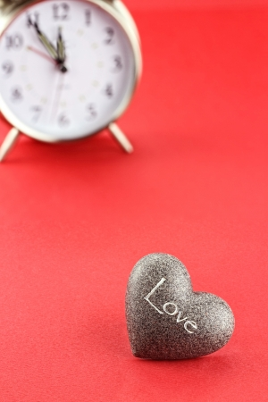 Conceptual image of heart with clock in background. Extreme shallow depth of field with selective focus on foreground. Stock Photo - 17103147