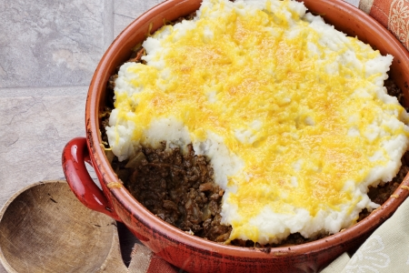 baked potatoes: Shepards Pie in a rustic casserole dish with part taken out exposing inside filling.