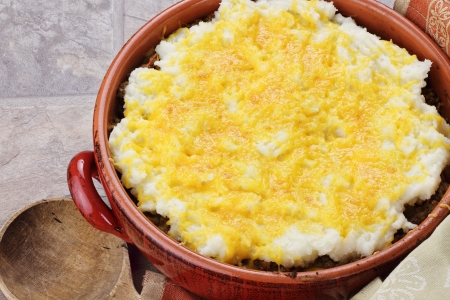 minced pie: Shepards Pie in a rustic casserole dish with wooden spoon.