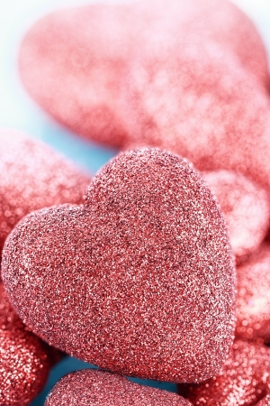 Sparkly red hearts over a blue background. Extreme shallow depth of field with selective focus on large heart in foreground. Stock Photo - 17412524