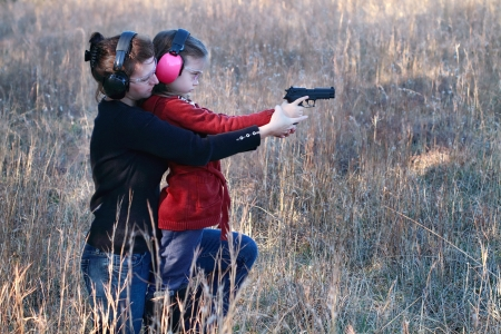 Mother teaching her young daughter how to safely and correctly use a handgun. Stock Photo