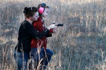 Mère enseigner sa petite fille comment utiliser correctement et en toute sécurité une arme de poing.