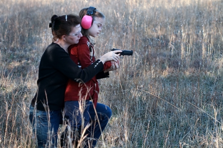 women with guns: Mother teaching her young daughter how to safely and correctly use a handgun. Stock Photo