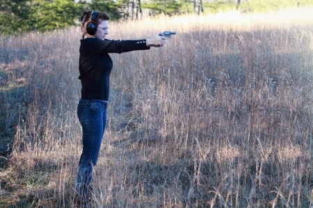 mujer con pistola: Madre que enseña a su hija cómo utilizar de forma segura y correctamente un arma de fuego.