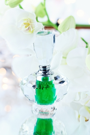 Beautiful bottle of perfume or essence with lovely white orchids  photo