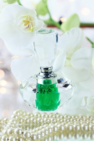 Beautiful bottle of perfume with vintage pearls and flowers. photo