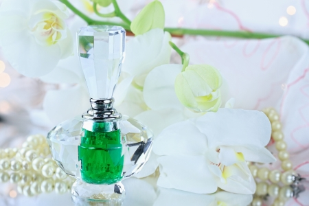 Beautiful bottle of perfume with lovely white orchids and pearls. photo