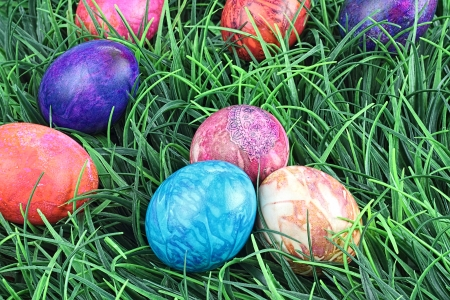 Hand painted tie dyed Easter eggs in the grass. Extreme shallow DOF.  photo