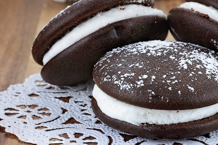 Macro image of three whoopie pies or moon pies with powdered sugar. Shallow depth of field. Stock Photo