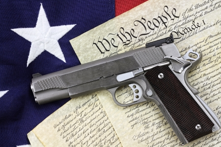 Handgun lying over a copy of the United States constitution and the American flag. Stock Photo