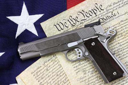 Pistolet leżący na kopię konstytucji Stanów Zjednoczonych i amerykańskiej flagi.