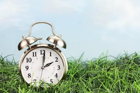despertador: Reloj en el césped. Horario de verano concepto del tiempo.
