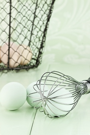 close up food: Fresh free range Ameraucana eggs in a whisk with brown eggs in a vintage basket in background