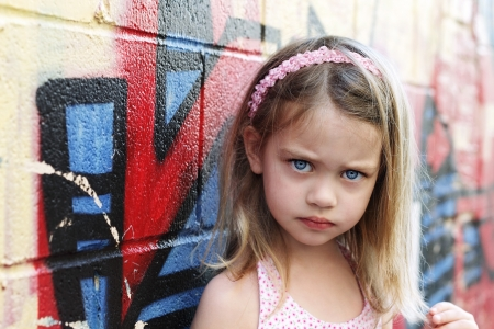 Worried little girl in an urban setting looking into the camera