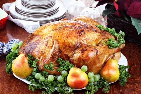 Thanksgiving or Christmas turkey dinner with fresh pears, grapes and parsley. Poinsettia flower arrangement, dishes and wine glasses in background.