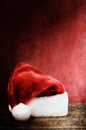 photo of object s: Santa Hat over a rustic wooden background with room for text